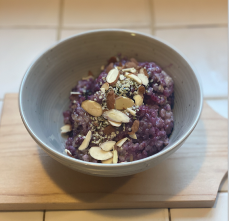 Leftover brown rice mashed into porridge with blueberries and almond slivers and hemp seeds